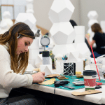 A young woman in a design studio works with material on a desk.