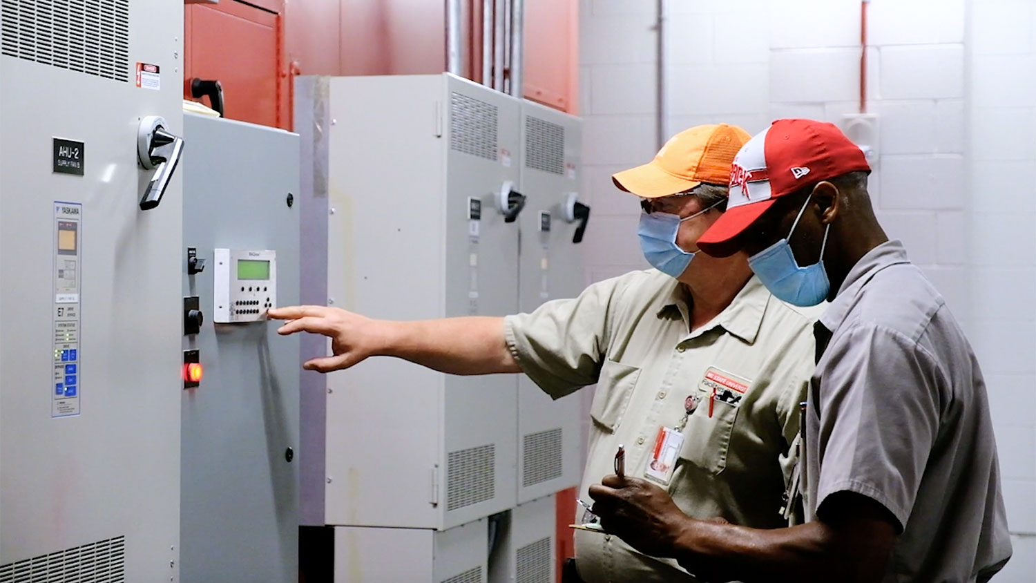 Two Facilities Division employees check the control panel of an HVAC system on campus