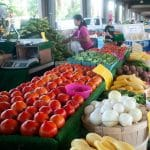 Colorful fruits and vegetables lined down an outdoor breezeway at the State Farmer's Market.