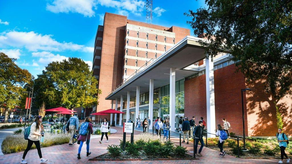An exterior shot of D.H. Hill Jr. Library with students flooding inside.