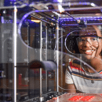 A young woman stands behind a 3D printer.