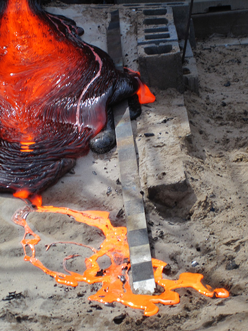 Metallic lava forms a volcano-like cooling peak while orange lava flows out of it onto dirt