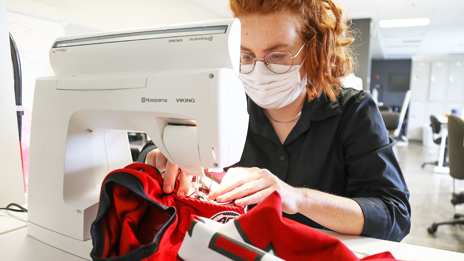 Bailey Knight sews a patch on a football uniform