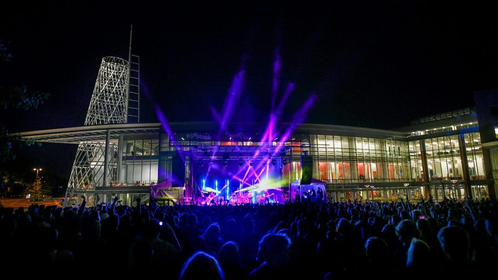 A large crowd watches a concert with brightly colored lights outside of Talley Student Union.