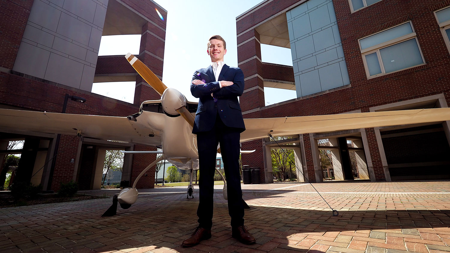 Goldwater Scholar Andrew Mistele in front of an airplane near the Engineering buildings on Centennial Campus