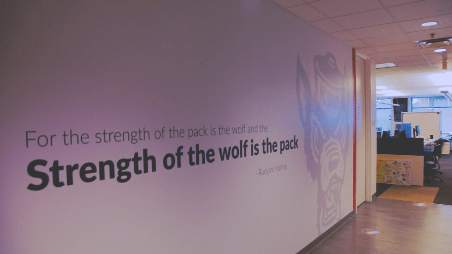 "A mural in the LexisNexis office's hallway that reads ""For the strength of the pack is the wolf and the strength of the wolf is the pack."""