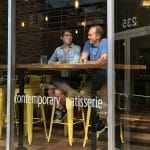Two people chat in window-facing seats at a downtown Raleigh bakery.