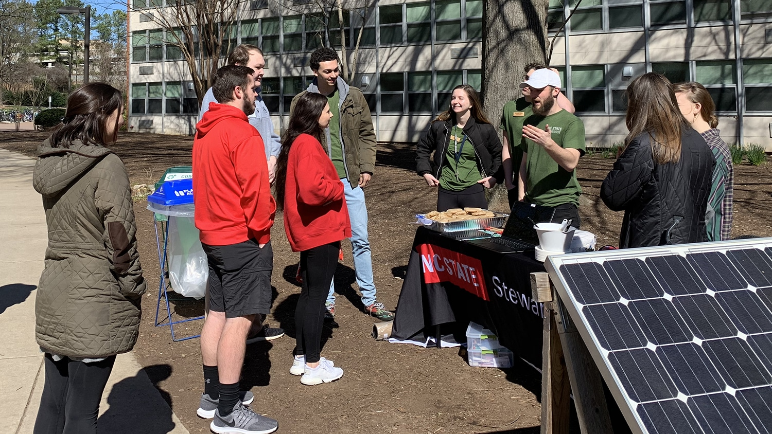 NC State Stewards, wearing matching green T-shirts, speak to a small group of fellow students outside next to a solar panel.