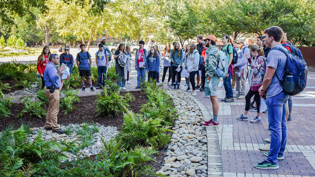 Students learn about water quality during an outside class through the Environmental First Year Program.