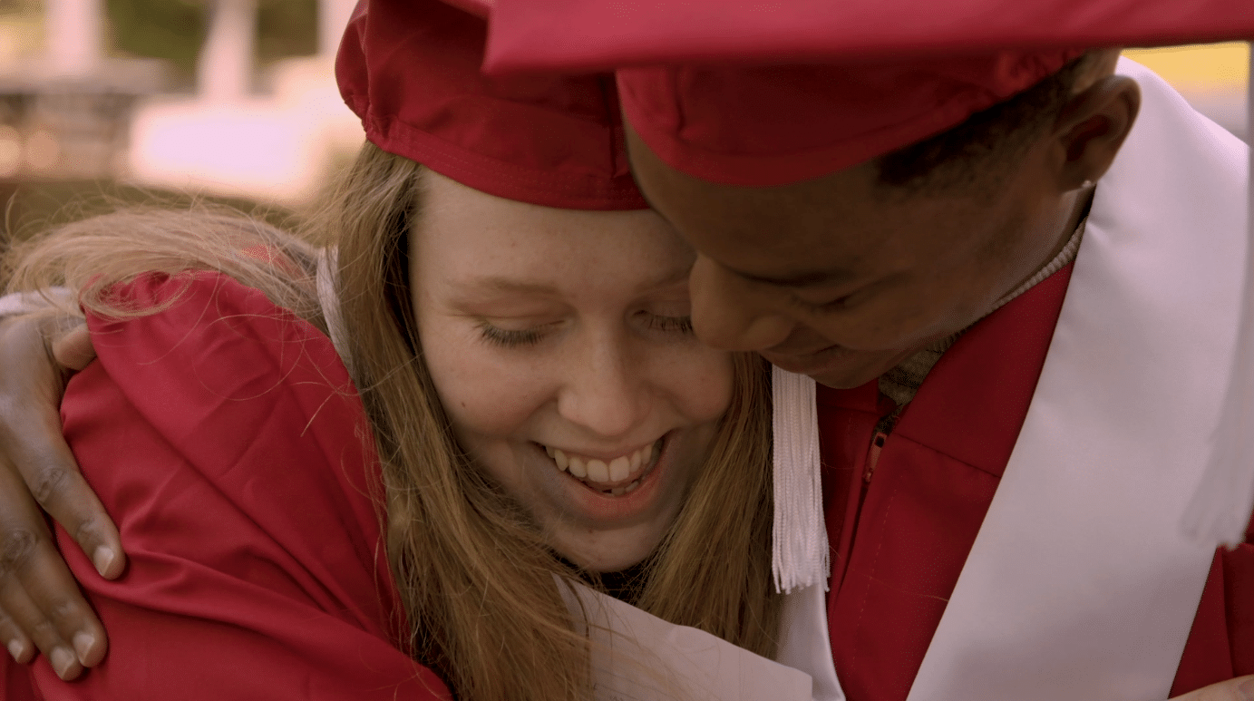 Sara Altman and Justin Mason share a hug while wearing their graduation caps and gowns.