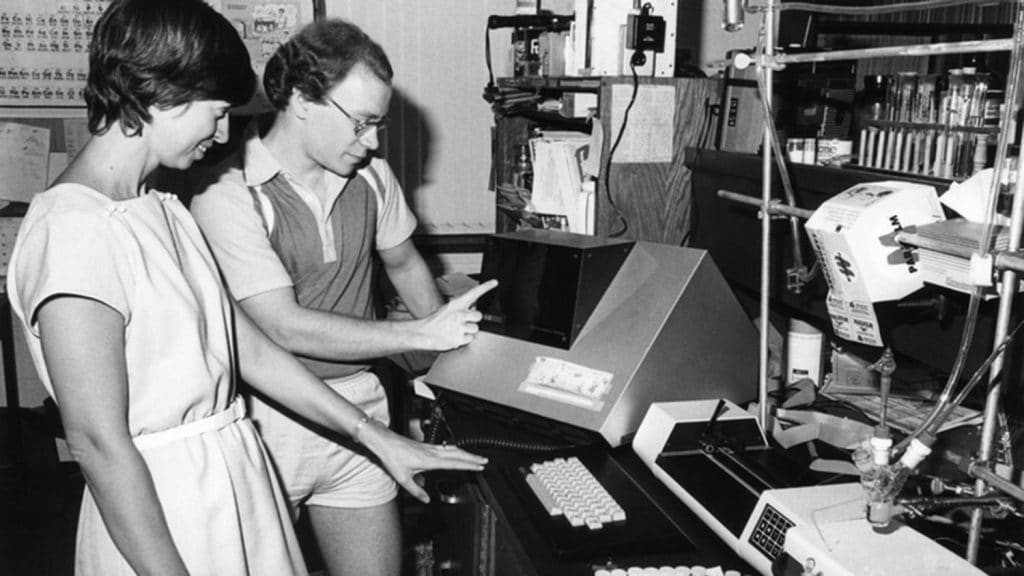 In 1980s photo, Marye Anne Fox examines lab equipment with unidentified colleague.