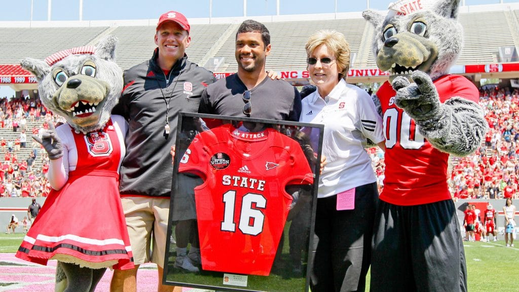 Wilson, center, at a ceremony honoring his jersey at the 2014 Kay Yow Spring Game. Wilson is flanked by Mr. and Ms. Wuf, football head coach Dave Doeren and former athletics director Debbie Yow.