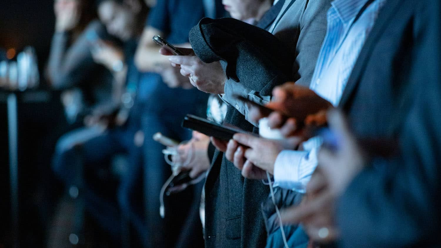 a crowd of people stand looking at their smartphones