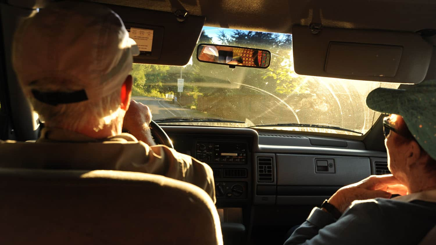 Older man and woman in front seat of a car.