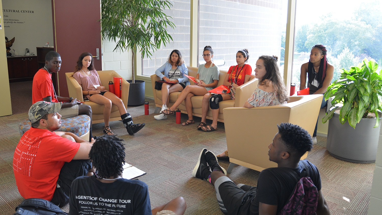 Diverse students sit in a circle talking
