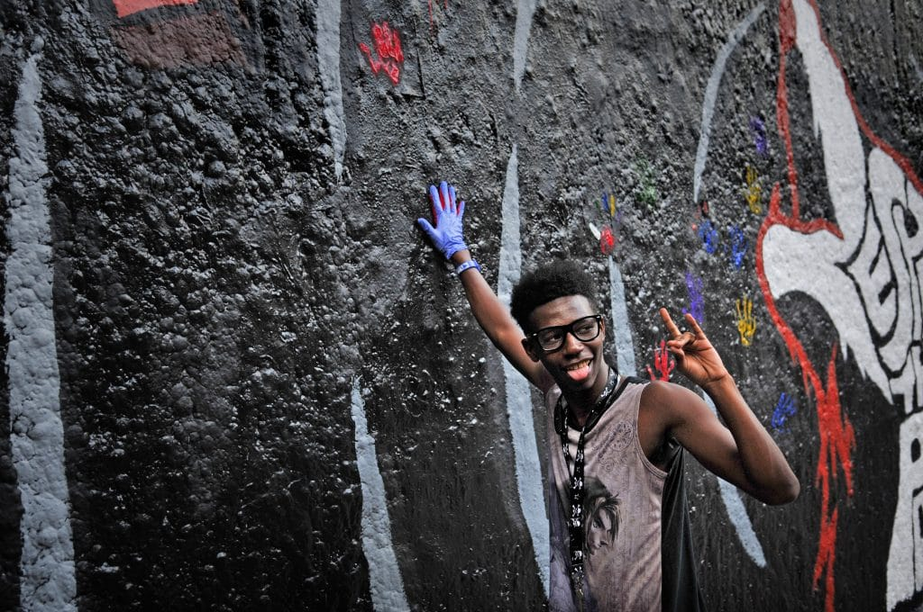 A young man makes a handprint on the wall at the Respect the Pack event.