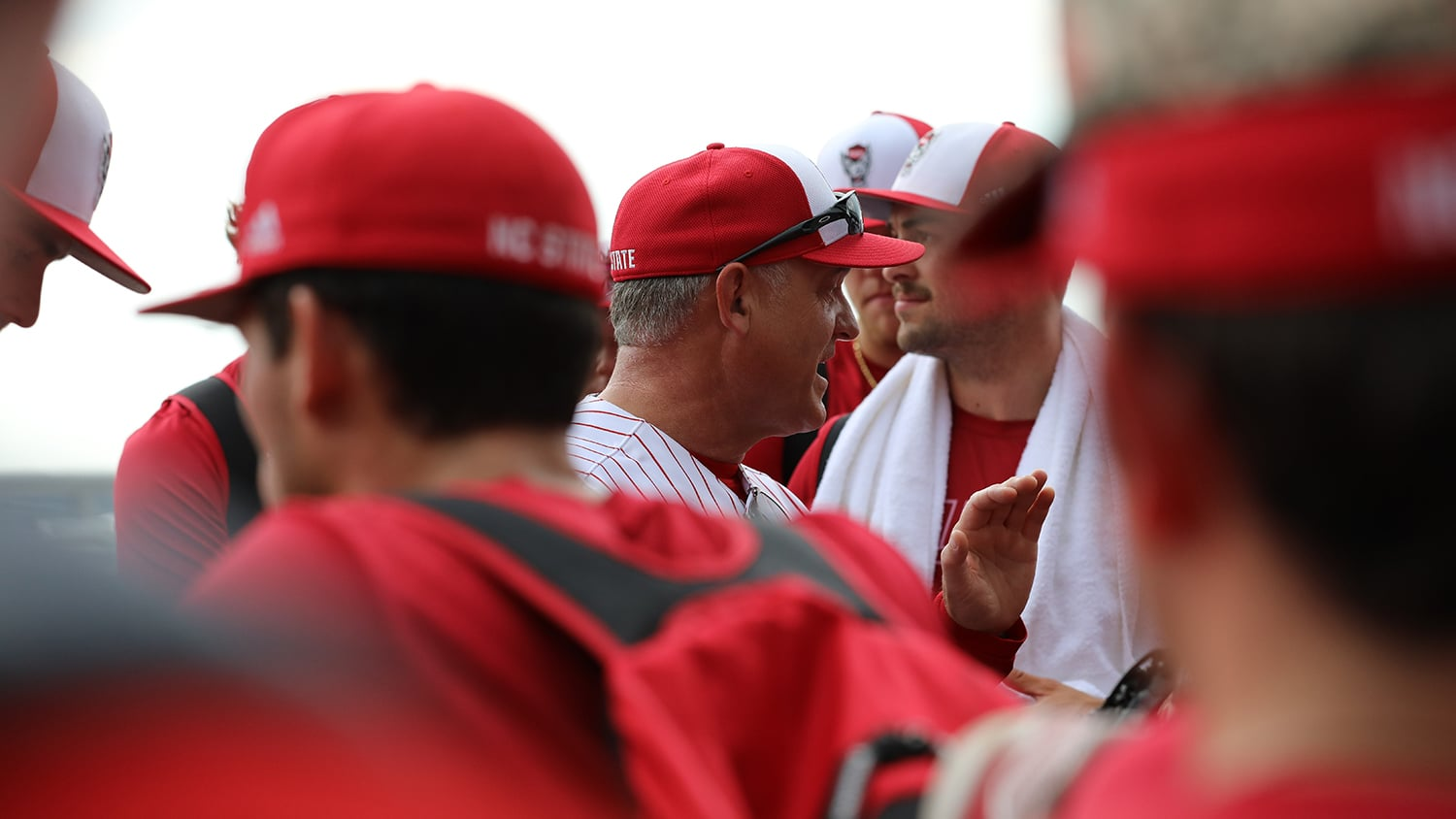 Coach Elliott Avent at practice in Omaha, surrounded by baseball players.