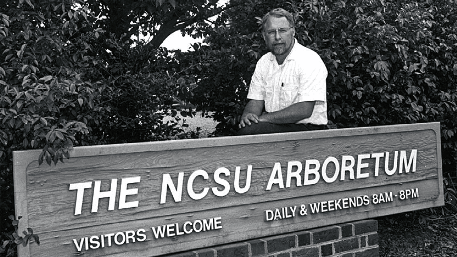 J.C. Raulston behind a sign identifying the NCSU Arboretum in the 1970s.