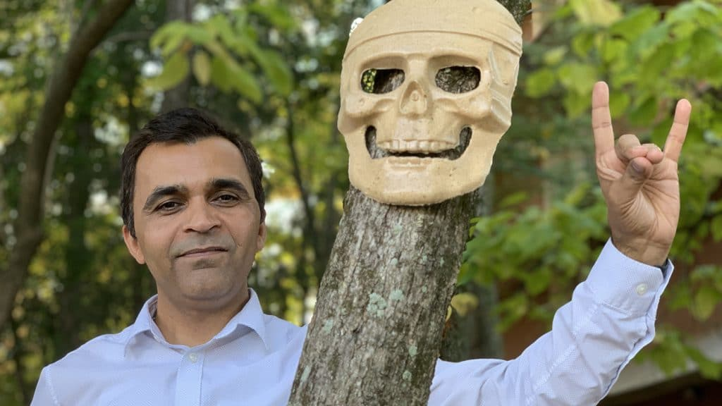 Lokendra Pal poses in the woods with a sample of the wood-based, Styrofoam-like material, which has been made into a skull mask and hung on a small tree.
