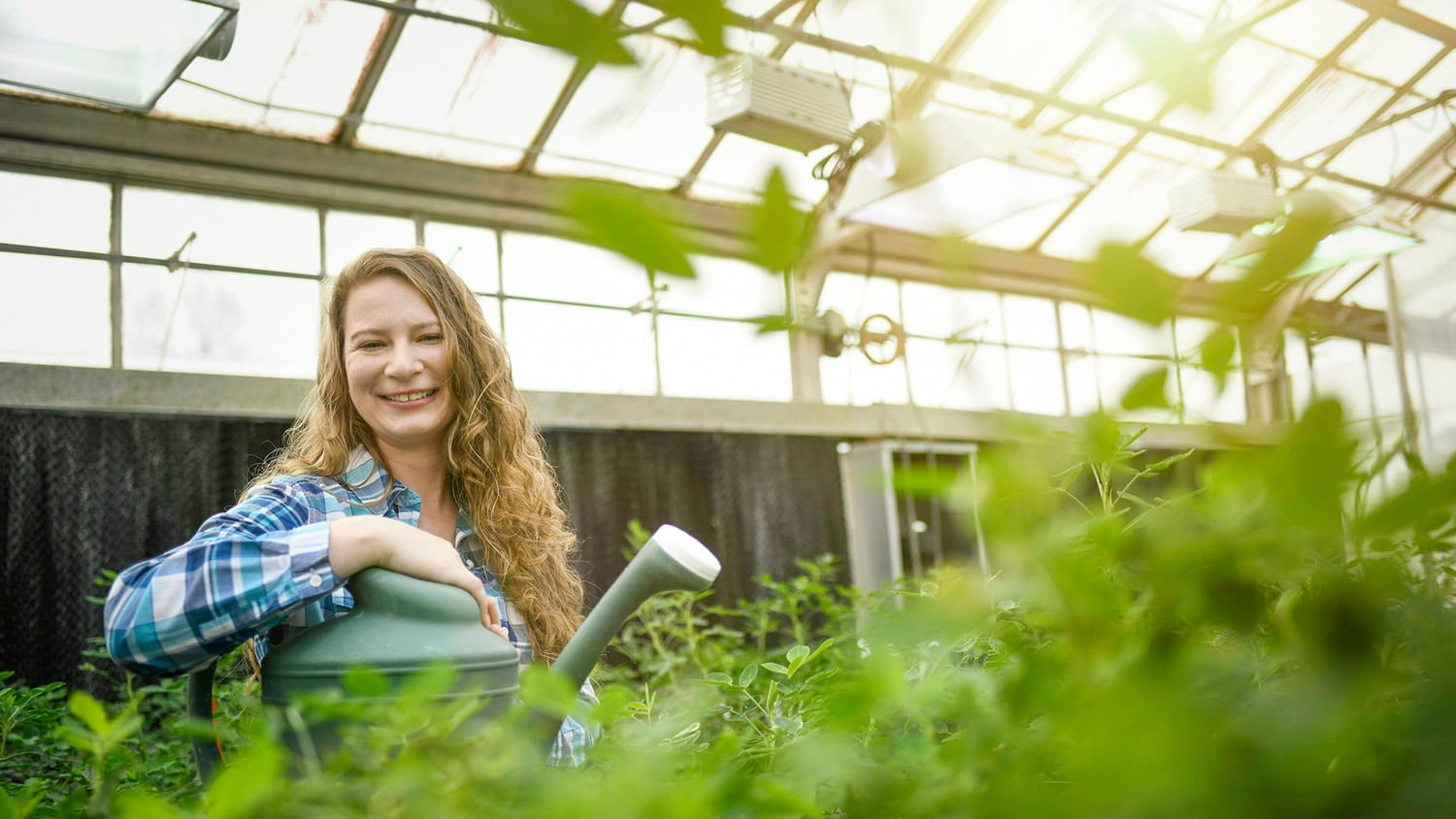 A student smiles from a greenhouse full of peanut plants.