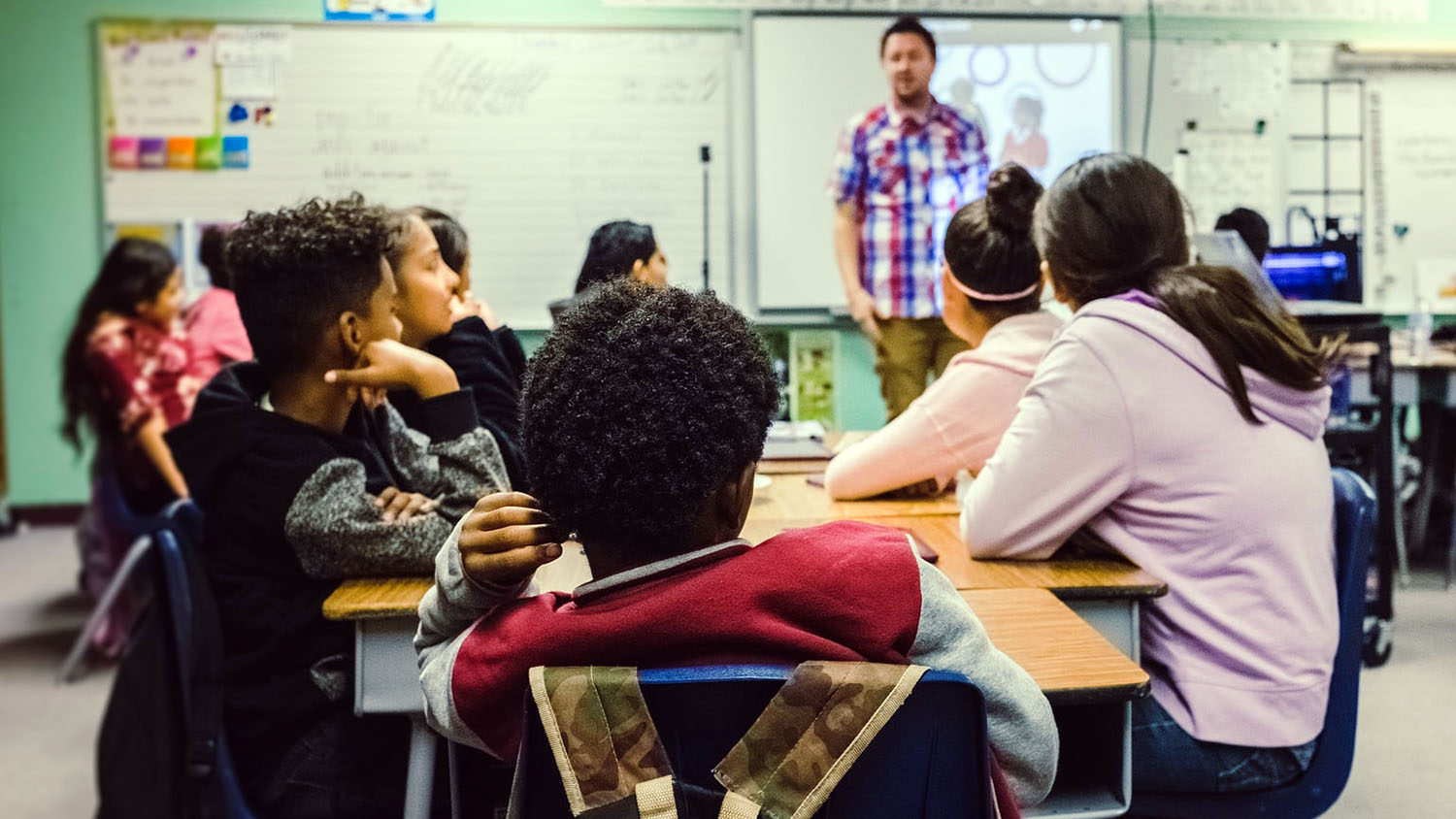 A multicultural mix of middle school students listen to a teacher in a classroom.