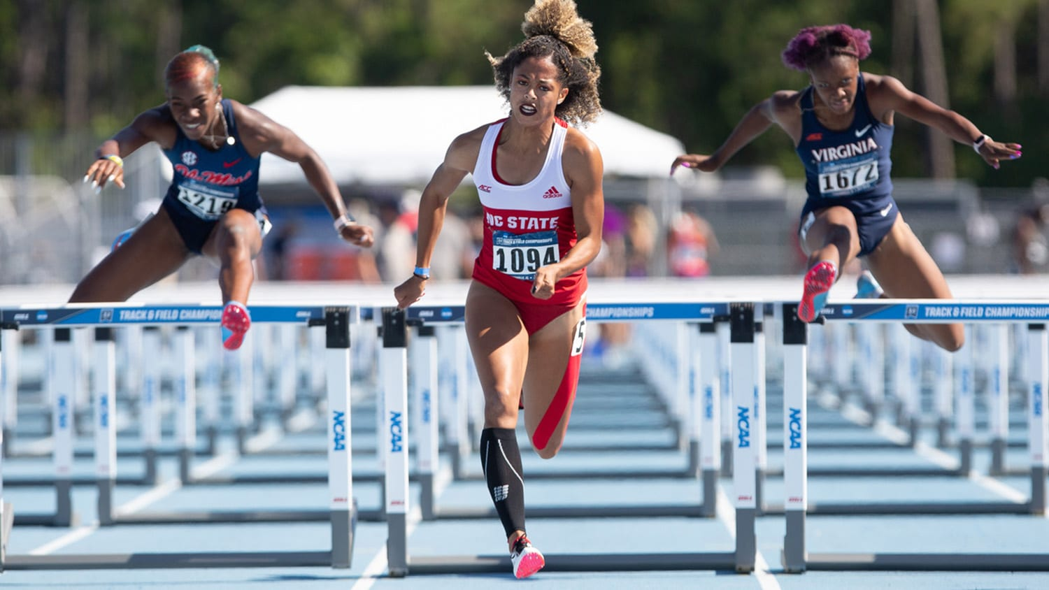 Gabrielle Cunningham jumps over a hurdle at a track and field event.