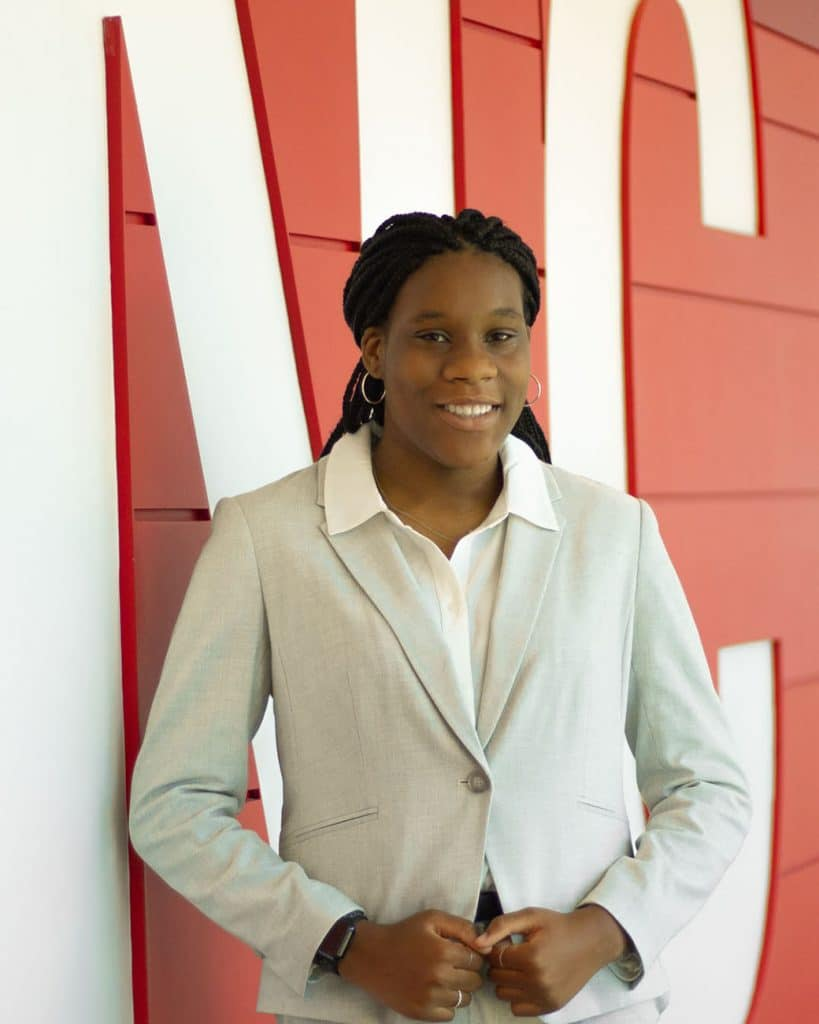 Kayla Alford, wearing a cream jacket, stands for a portrait in front of a red and white background.