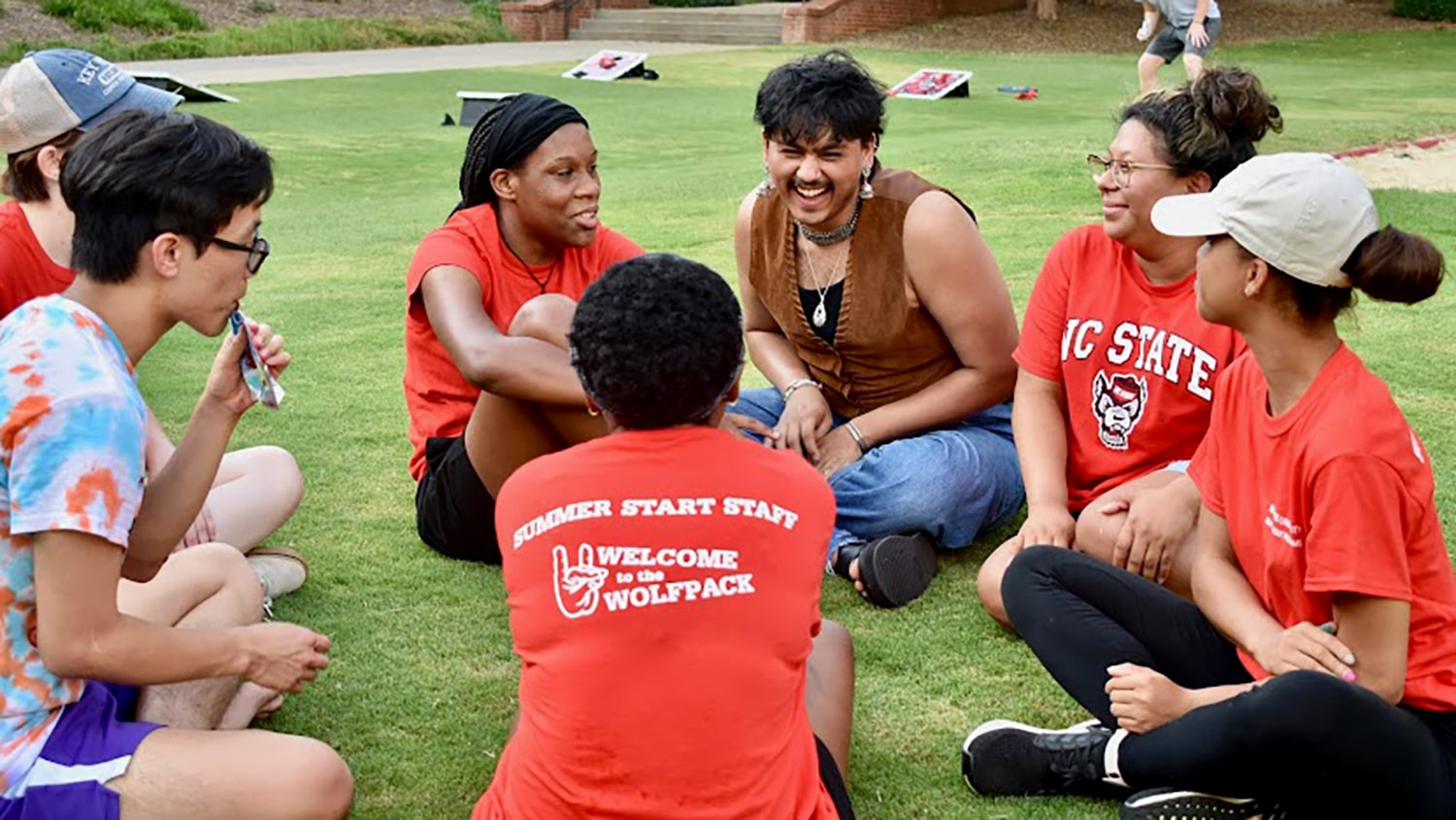 Students participating in Summer Start sit in a circle on the lawn outside of Tucker Hall and socialize during a Summer Start event.