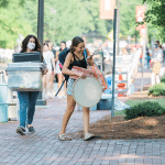 A mother and daughter carry items to a residence hall.