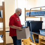 Chancellor Randy Woodson helps unpack items in a dorm room.
