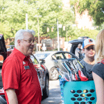 Chancellor Randy Woodson stops to talk to a family unpacking items on move-in day.