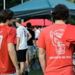 Students in red shirts walk through RecFest.