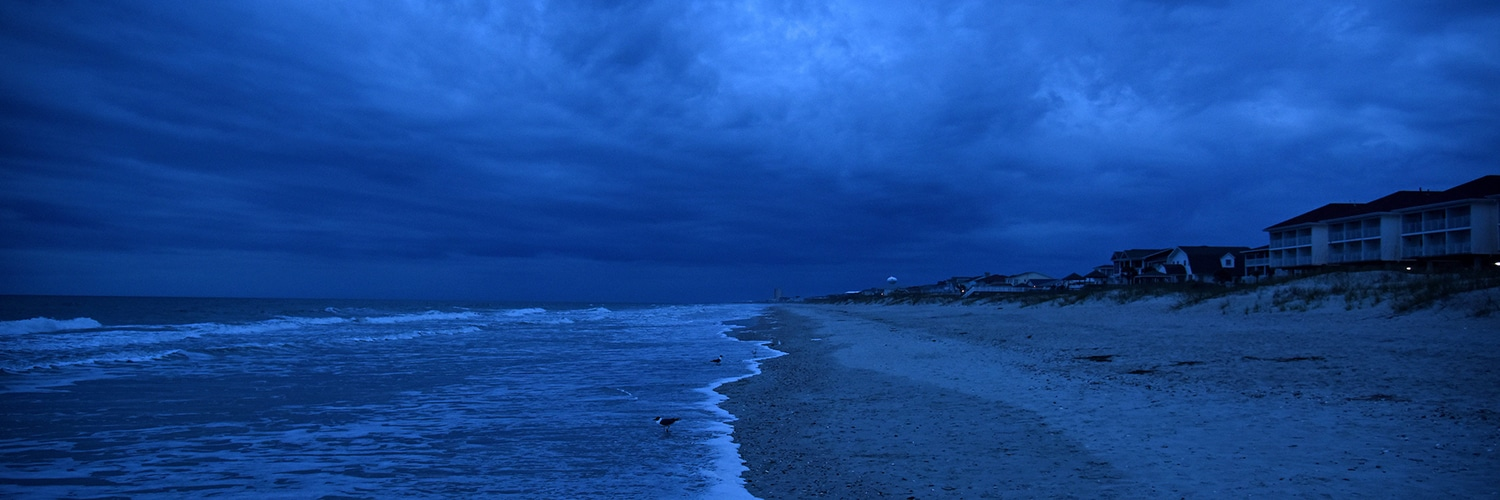 Storm clouds roll across Ocean Isle at dawn.