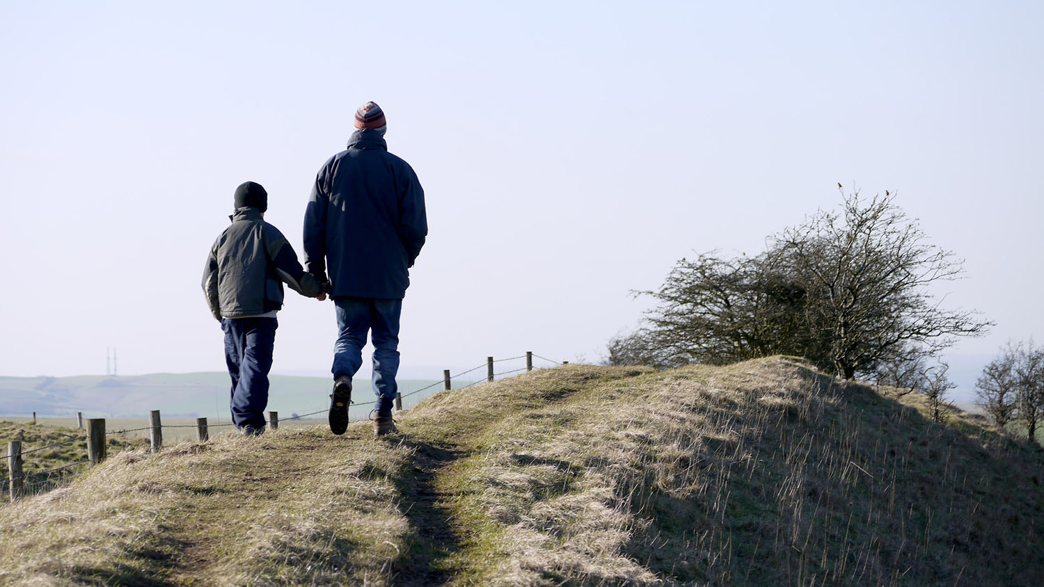 man and boy in silhouette, going for a walk together