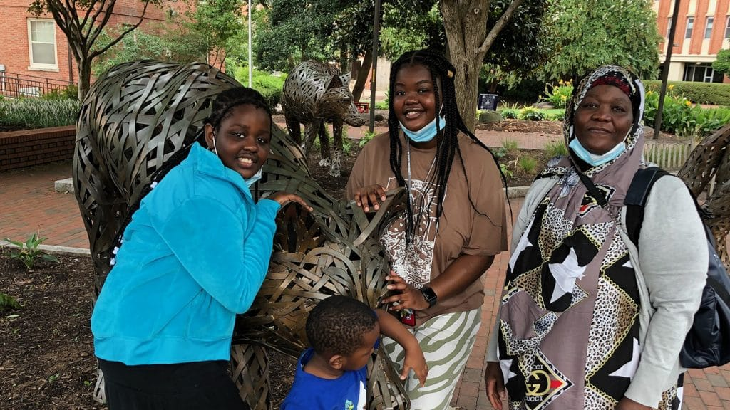 Faduma Osman with her sister, brother and mother at the copper wolf statues on campus