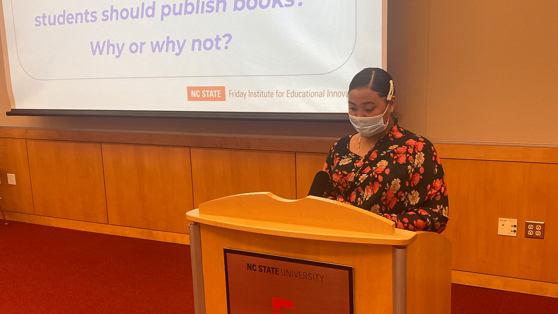young woman reading at a podium