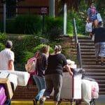 Families wheel possessions toward residence halls.