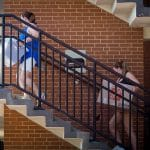 A mother and daughter carry boxes up stairs at a residence hall.