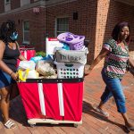 A mother and daughter wheel a cart of possessions toward a dorm.
