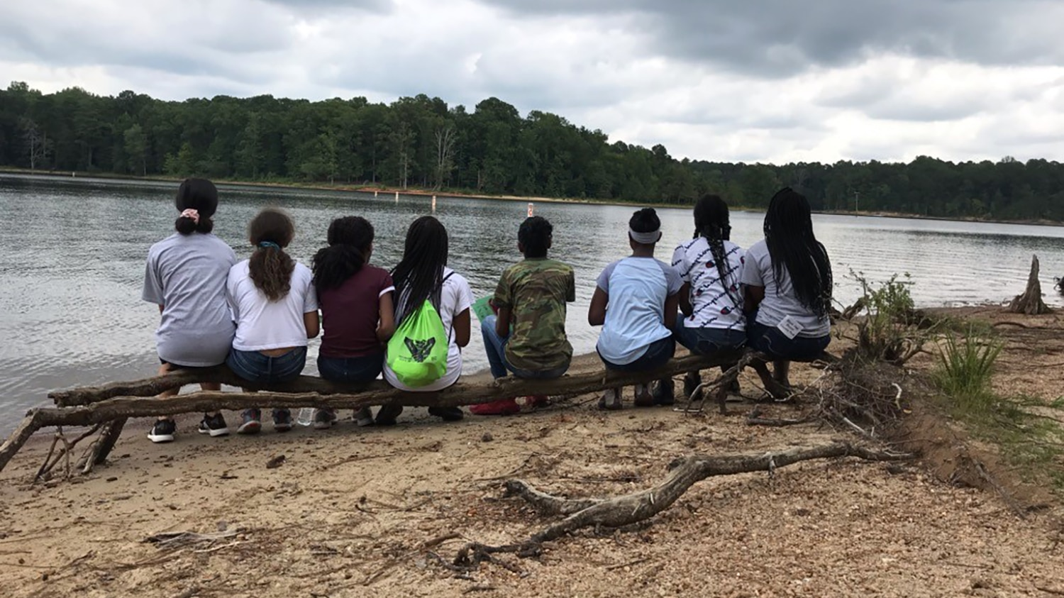 A group of middle school students sit on a log and look out onto a lake.