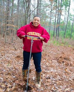 Zakiya Leggett — in a red Tuskegee University hoodie, jeans and brown boots — takes a soil sample outside in a wooded area.