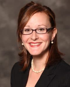 Jennifer Runkle, wearing a black blazer and a string of pearls, poses for a headshot.