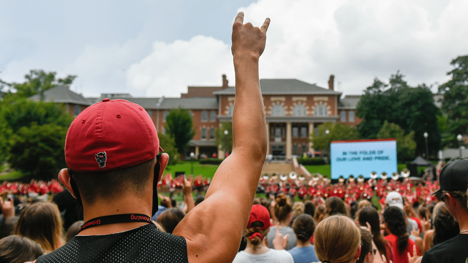 A student holds up wolf hands above a crowd.