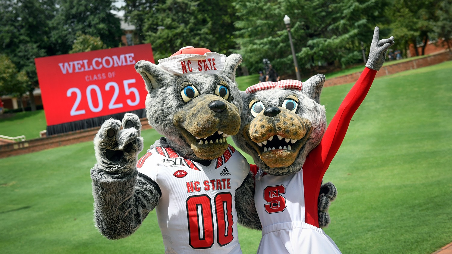 """Mr. and Ms. Wuf pose in front of a sign reading """"Welcome Class of 2025."""""""