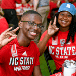 A mother and son hold up wolf hands and smile.