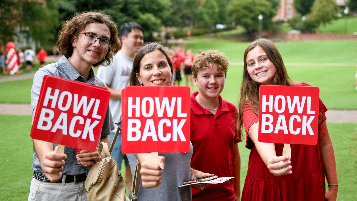 """A family holds up signs that say """"Howl Back"""" during the Legacy Luncheon."""