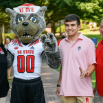 A family poses for a photo with Mr. Wuf, throwing up wolf hands.