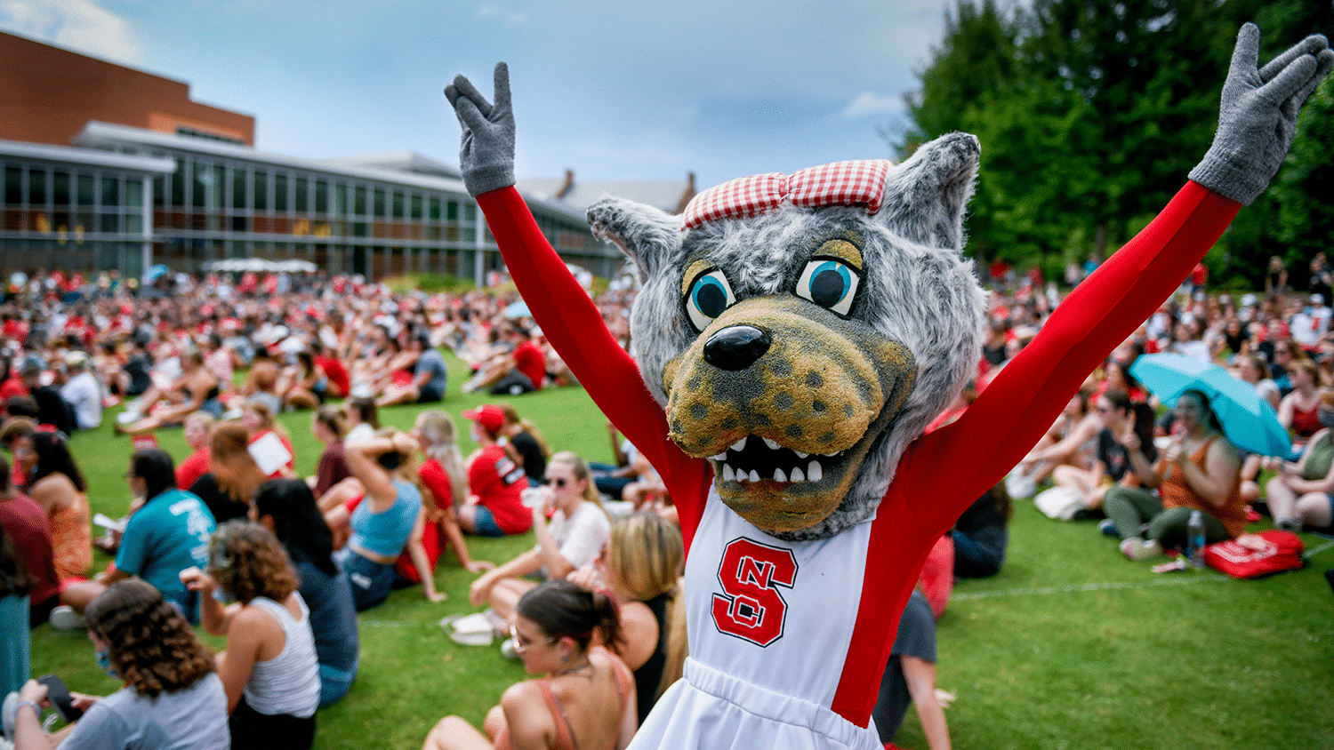 Ms. Wuf poses with wolf hands at convocation.