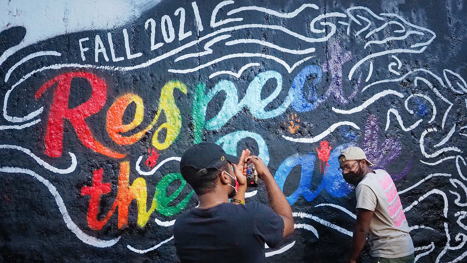 A student takes a photo of another student leaving their handprint on the Respect the Pack mural.