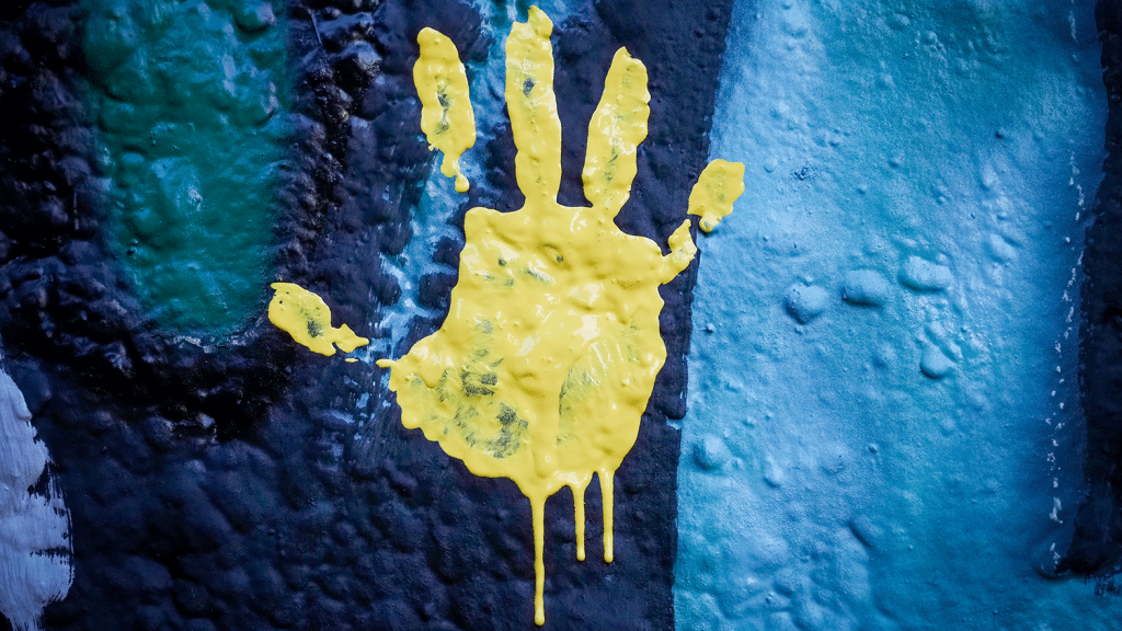 A yellow handprint on the Respect the Pack mural.